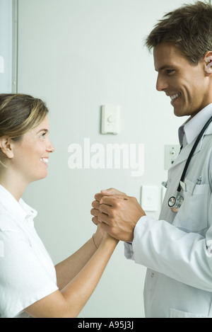 Doctor and woman standing face to face, holding hands and smiling at each other - Stock Photo