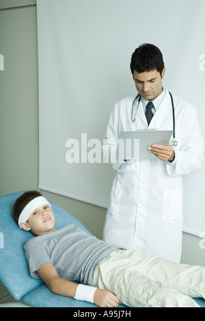 Boy lying on examination table with bandage on forehead and arm, doctor writing on clipboard - Stock Photo