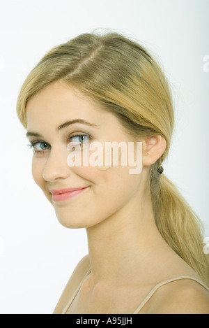 Teenage girl with dollop of foundation on cheek, smiling at camera - Stock Photo