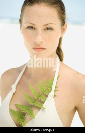 Young woman wearing bathing suit, fern leaf in top - Stock Photo
