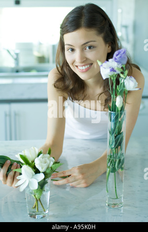 Young woman smiling, with fresh flowers in vases, portrait - Stock Photo