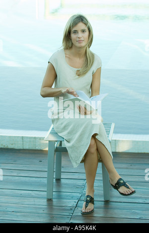 Woman sitting and holding book, water in background - Stock Photo