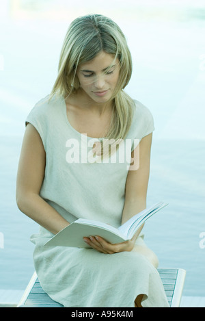 Woman sitting, reading book, water in background - Stock Photo