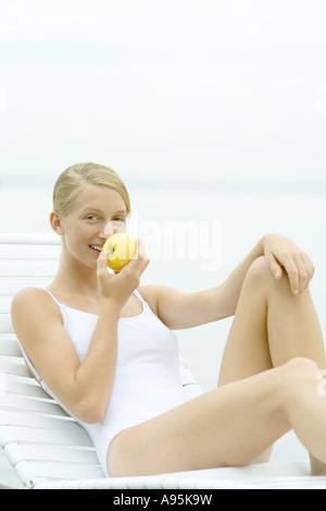 Teenage girl wearing bathing suit, sitting in lounge chair, eating apple - Stock Photo