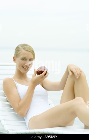 Teenage girl wearing bathing suit, sitting in lounge chair, holding apple - Stock Photo