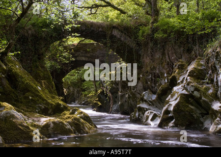 tranquil scene of the fast flowing Conwy river flowing beneath a pack horse bridge outside Penmachno, Betws-y-Coed - Stock Photo