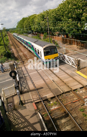 train passing over a road at a manned rail crossing - Stock Photo