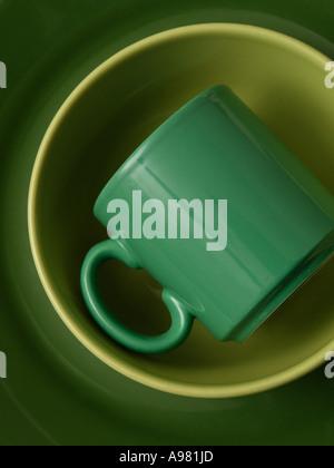 Stoneware earthenware crockery in various shades of green plate bowl mug - Stock Photo