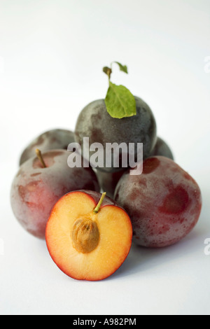 Several whole plums and one half plum FoodCollection - Stock Photo