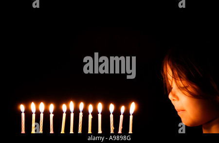 Girl aged 3 blows out 12 candles - Stock Photo