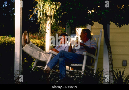 Retired couple sitting in rocking chairs on front porch - Stock Photo