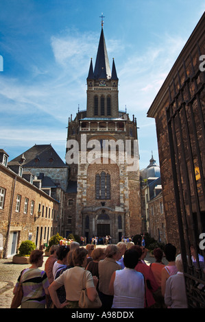 Aachen, Germany - Tourists with tour guide at Aachen Dom cathedral - Stock Photo
