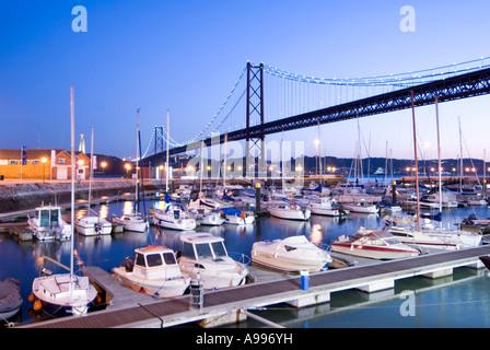 Suspension bridge of Ponte 25 de Abril spanning the docks of Doca de Santo Amaro in the Alcantara area of Lisbon - Stock Photo