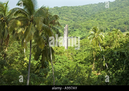 The rain forest encroaching on the ruins of a tall chimney stack belonging to an old Sugar Plantation, St Kitts - Stock Photo