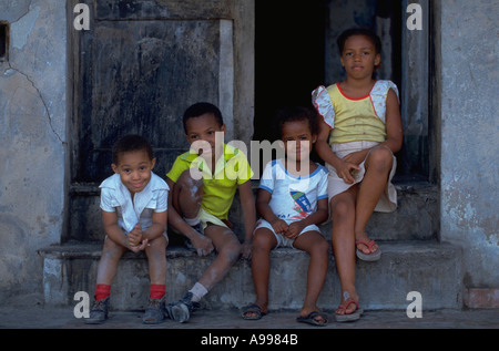 Four children sit on the front stoop of their home in a building on the Malecon waterfront drive Havana Cuba - Stock Photo