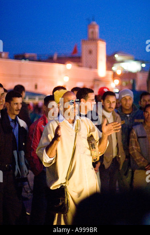 Crowd gathered around a popular storyteller and musician performing on the central square of Djemaa El Fna in Marrakesh - Stock Photo