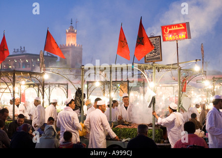 Busy open air food stall with Moroccan flags on the central square of Djemaa El Fna in Marrakesh - Stock Photo