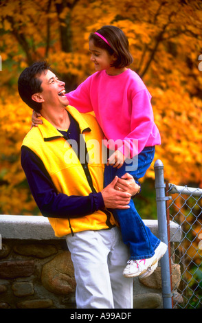 Hispanic father holding his young daughter and laughing - Stock Photo