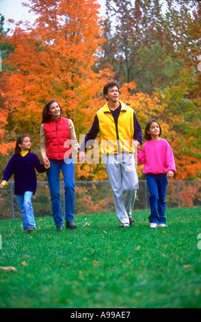 Hispanic couple and their two daughters holding hands and walking through the park - Stock Photo