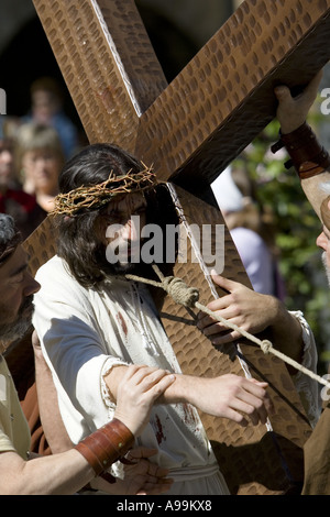 Actor playing Jesus Christ carrying a wooden cross during ...