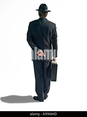 Business man in black suit with black fedora hat and briefcase with fingers crossed behind his back - Stock Photo