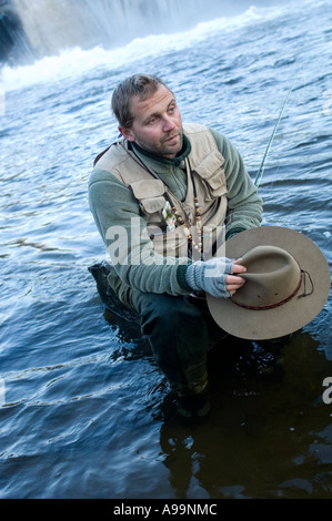 Man sitting on a rock while fishing holding hat in a river looking tired or worn out - Stock Photo