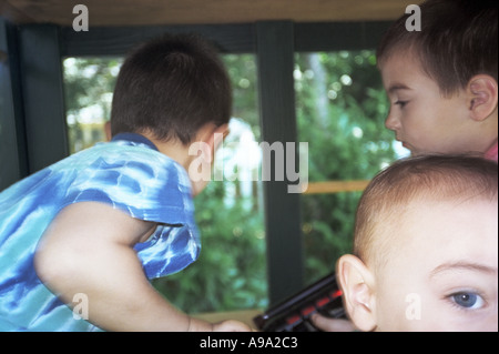 Children playing outside in playhouse - Stock Photo