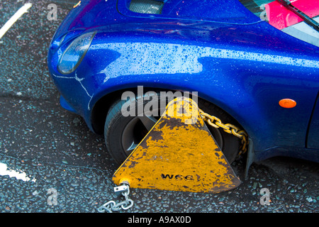 Wheel clamp on a car in London England - Stock Photo