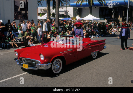 St Patricks Day Parade in Hermosa Beach, California - here the Red Hat Society represented in a stylish Ford Thunderbird - Stock Photo