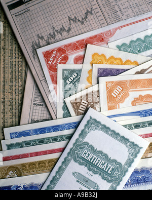 PAPER BONDS STOCK CERTIFICATES WITH NEWSPAPERS - Stock Photo