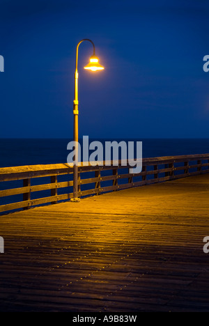 Lone Lamp Post On Board Walk With Light Glowing At Night Near Ocean, Ventura Pier California USA - Stock Photo