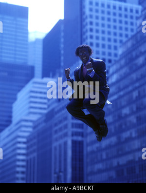 AIRBORNE OFFICE WORKER JUMPING IN MID AIR OFFICE BUILDINGS  MANHATTAN NEW YORK CITY USA - Stock Photo