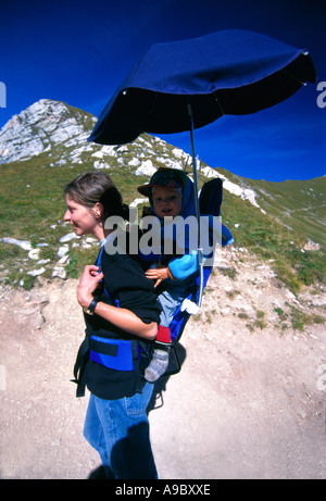 Hiker mother carrying the baby with umbrella down hill - Stock Photo