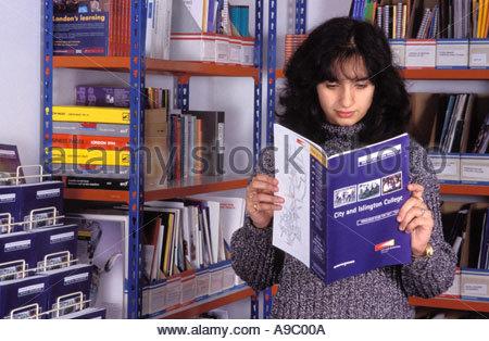 Student reading City Islington College prospectus in careers office - Stock Photo