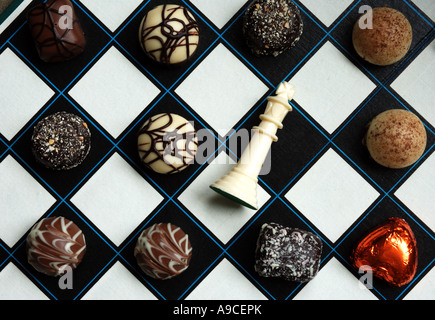 Fancy chocolates on a chess board with king resigned - Stock Photo