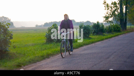 Woman riding bicycle down country road. Highway 72 between Lodz and Rawa Maz. Poland - Stock Photo