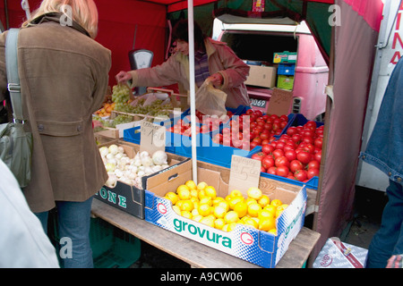 Woman buying produce at the outdoor sidewalk market. Lodz Poland - Stock Photo