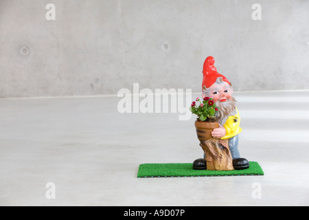 garden gnome holding potted flower - Stock Photo
