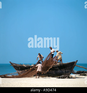 Fishermen folding up their nets on a fishing boat on a beach in South Goa, India - Stock Photo