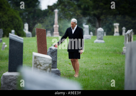 A senior woman places a rose on a gravestone - Stock Photo