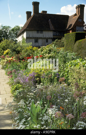 House behind flowering mixed border. Great Dixter Gardens, Sussex, United Kingdom - Stock Photo