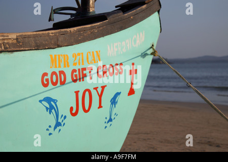 Local fishing boat with decorations and messages painted on the bow, on the beach in Palolem, Southern Goa, India - Stock Photo