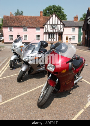 Lavenham Suffolk three 3 touring motorcycles parked with typical half timbered cottages beyond - Stock Photo