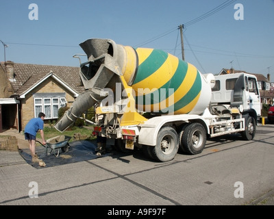 Essex ready mixed concrete lorry discharging load into wheelbarrows for use in domestic property extension - Stock Photo