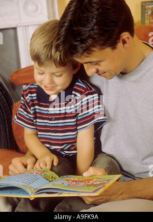 Father with his son looking at a picture book together - Stock Photo