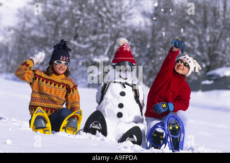 two girls wearing snowshoes, sitting beside a snowman, throwing snow balls. - Stock Photo
