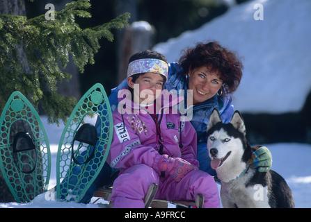 woman, siberian husky and girl on sled. - Stock Photo