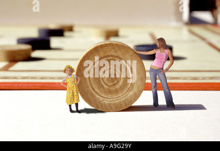 woman and  girl standing in front of a gigantic Checkers board game - Stock Photo