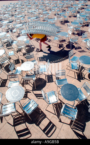 A young man hauls a stack of 16 metal chairs across the terrace in front of Gemini Lounge and Beach Bar on Brighton - Stock Photo