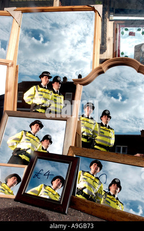 Two uniformed Police officers. one male one female,  on foot patrol reflected again and again in mirrors in a shop - Stock Photo